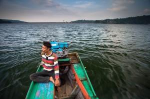 Pa Asep, duduk diperahu dengan latar belakang Waduk Jatiluhur, Purwakarta