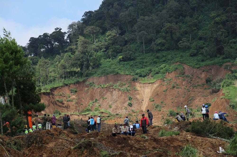 Warga dan relawan menyaksikan proses pencarian korban.
